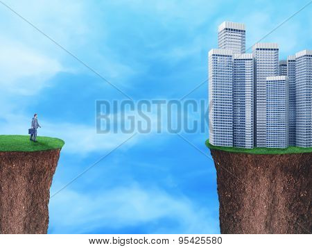Businessman on the edge looks at downtown