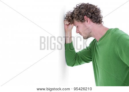 Sad casual man leaning against wall on white background