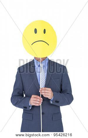a young businessman holding sad smiley faced balloon on white background