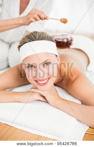 Mid section of therapist waxing womans back at spa center