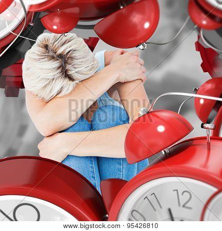 Depressed woman hiding her head against grey vignette