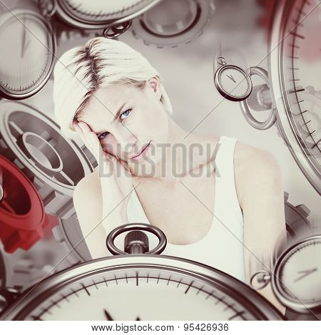 Depressed blonde woman with hand on temple against grey vignette
