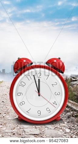 Alarm clock counting down to twelve against stony path leading to misty cityscape