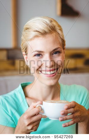 Pretty blonde looking at camera and holding cup of coffee at the cafe