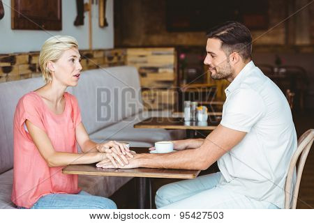 Cute couple on a date holding hands and discussing at the cafe