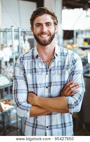 Selfassured waiter smiling in front of his bakery