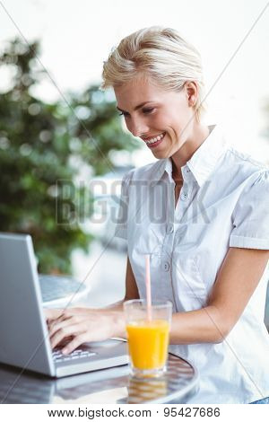 Happy pretty woman using her laptop computer in a cafe