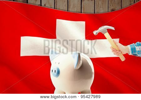 hand holding hammer against digitally generated swiss national flag