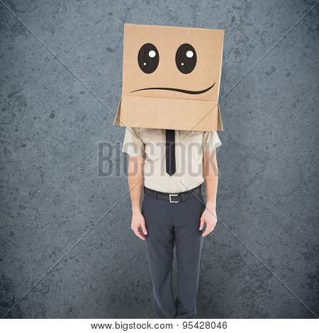 Businessman standing with box on head against dirty old wall background