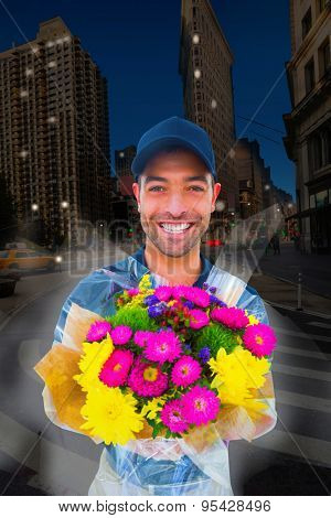 Happy delivery man holding bouquet against city at night