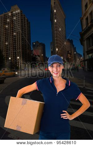 Happy delivery woman holding cardboard box against city at night