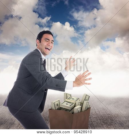 Excited businessman catching against blue sky