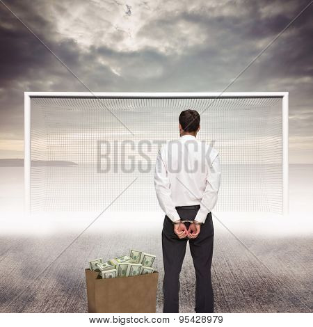 Rear view of young businessman wearing handcuffs against grey sky
