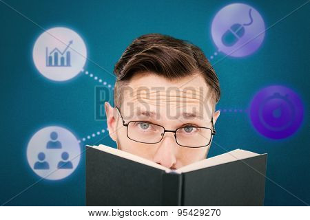 Young geek looking over black book against blue background