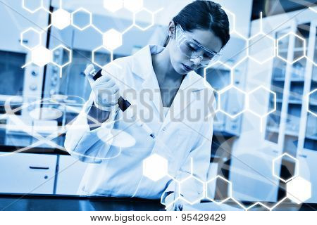 Science graphic against serious scientist pouring a liquid in an erlenmeyer flask