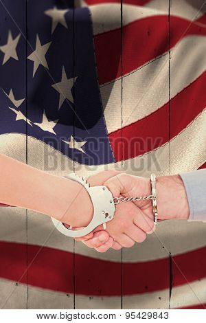 Handcuffed business people shaking hands against white wood