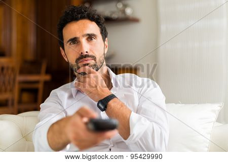Portrait of a man choosing a program to watch on television