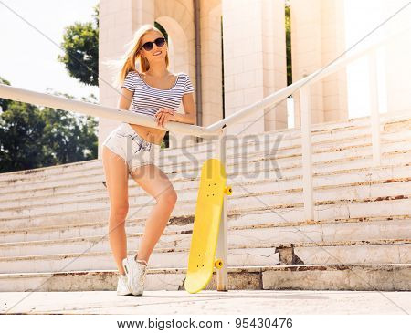 Full length portrait of a cute female skater in sunglasses standing outdoors
