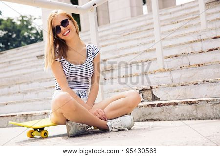 Happy female skater in sunglasses sitting on skate outdoors