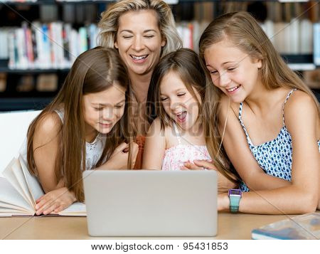 Little girls and their mum with a laptop in library