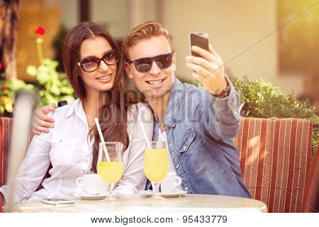 happy couple with sunglasses taking selfie in a cafe