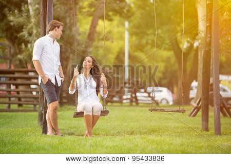 Attractive couple in park on swing, girl sitting on swing man standing next her