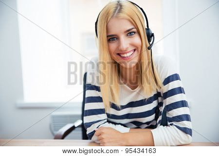 Smiling female operator with headset looking at camera in office