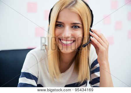 Smiling beautiful girl with headset sitting at the table in office