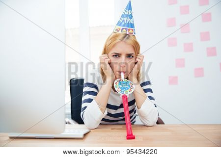 Young girl sitting at the table with party hat in office and blows whistle