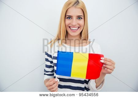 Smiling young girl holding Romanian flag over gray background. Looking at camera
