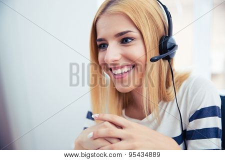 Happy young female operator in headphones working at office