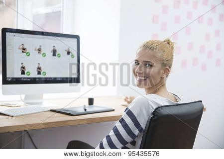 Smiling female photo editor sitting at the table in office and looking at camera