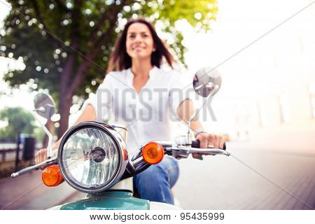 Smiling young woman on a scooter outdoors. Focus on scooter