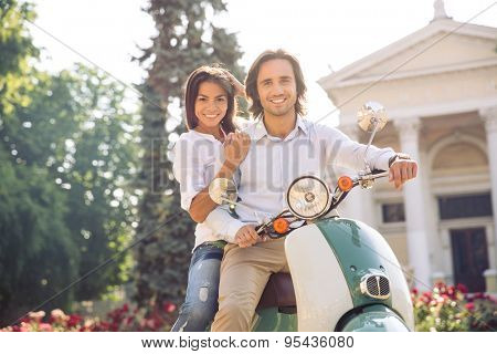 Young european couple on scooter in the town