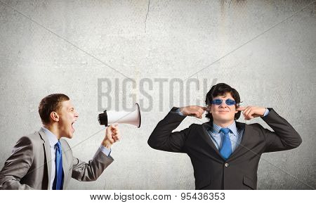Young furious woman screaming agressively in megaphone