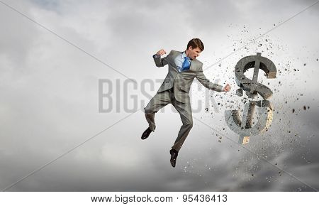 Businessman breaking stone dollar symbol with karate punch