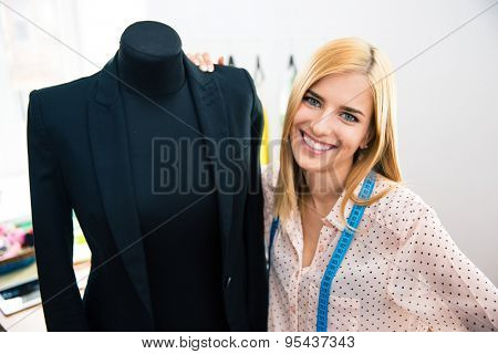 Smiling female tailor standing holding mannequin in jacket and looking at camera