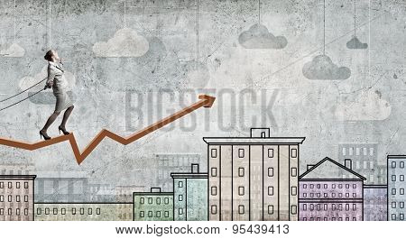 Young businesswoman with ropes on hands standing on graph