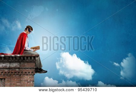 Young man in super hero costume sitting on roof