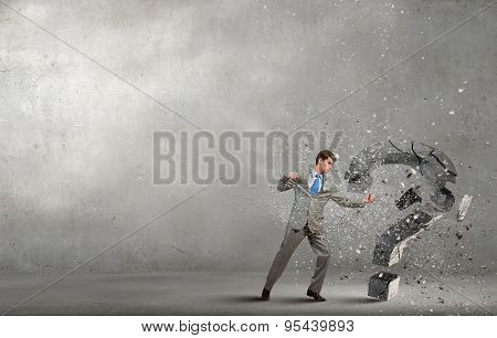 Businessman breaking stone question mark with karate kick