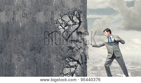 Young businessman in anger crashing cement wall
