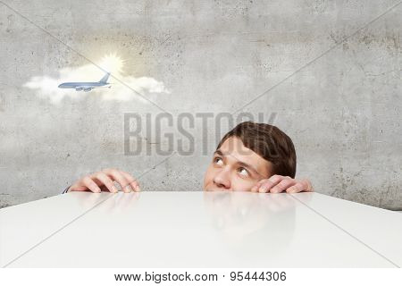 Young man looking from under table on flying airplane