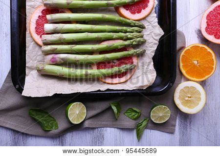 Fresh asparagus and grapefruit on pan on color wooden background