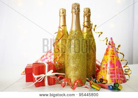 Decorative champagne bottles with serpentine on light background
