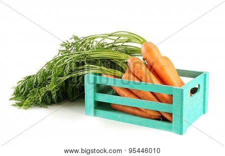 Fresh carrots in wooden crate isolated on white