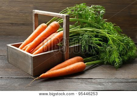 Fresh organic carrots in crate on wooden background