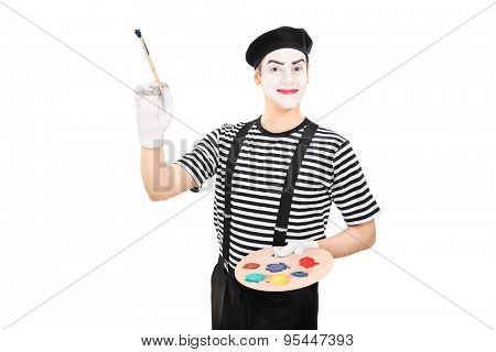 Young male mime artist holding a paintbrush and a color palette isolated on white background
