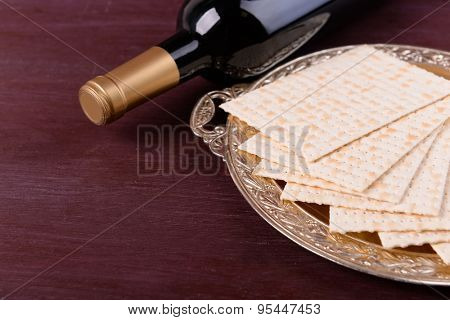 Matzo for Passover on metal tray with bottle of wine on table close up