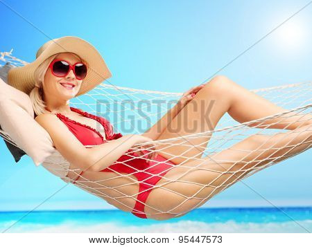 Beautiful woman in a red swimsuit lying in a hammock at a beach on a beautiful summer day