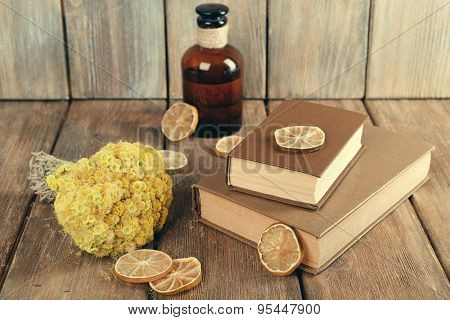 Old books with dry flowers and lemon on wooden background